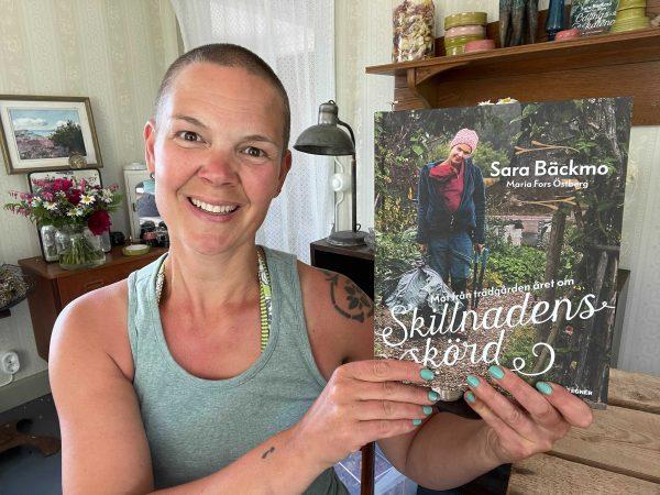 Sara håller sin bok Skillnadens Skörd