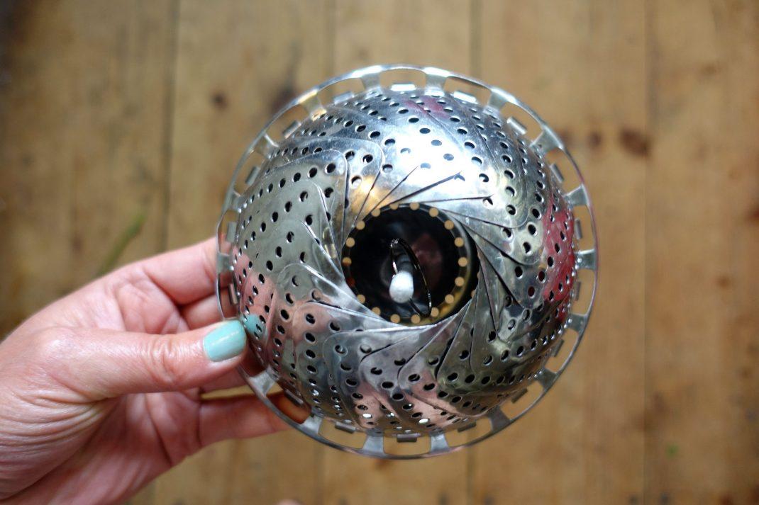 En liten pryl med hål i, rund, i rostfritt stål.