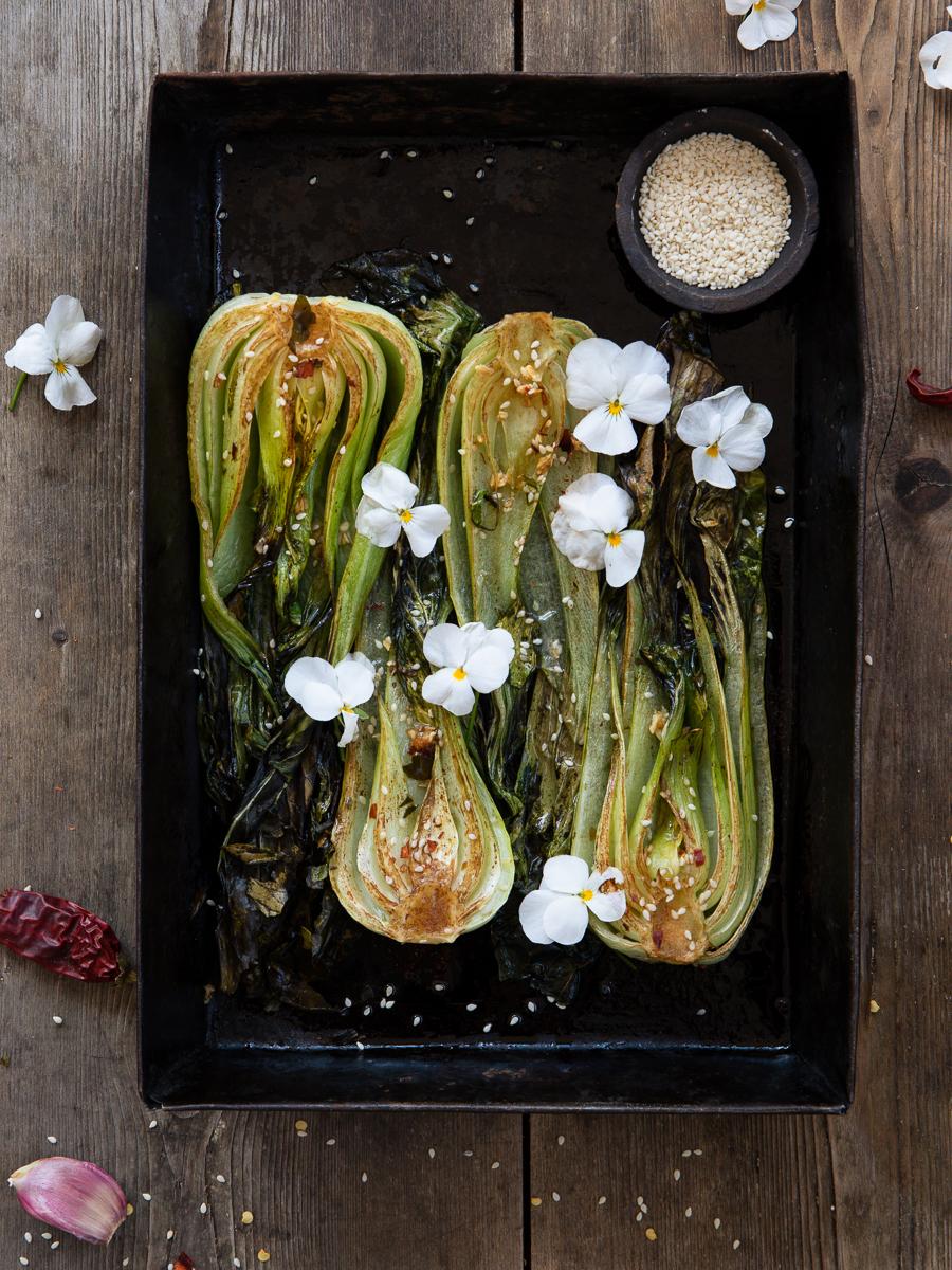 Ugnsrostad pak choi på en plåt med blommor och sesamfrön.