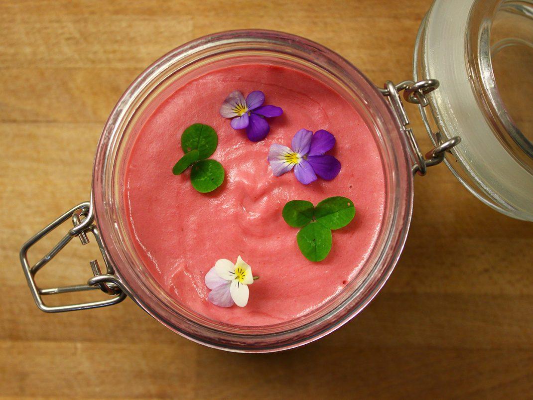 En hallonröd dessert med blommor och klöver serverad i glas.