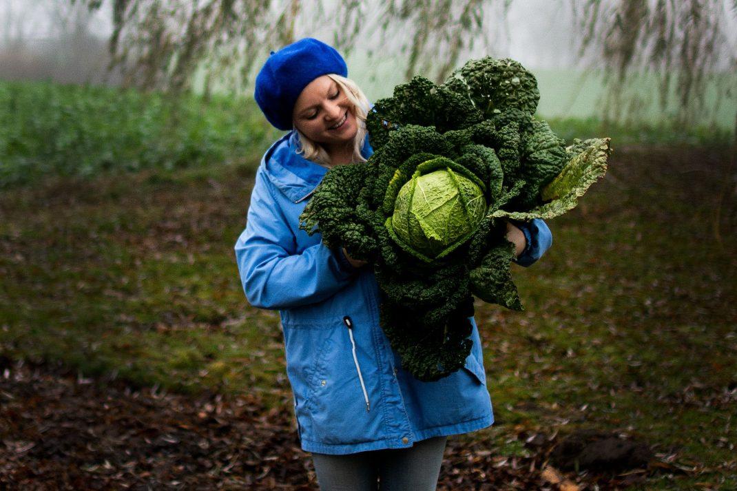 En tjej i blå jacka håller ett stort kålhuvud.