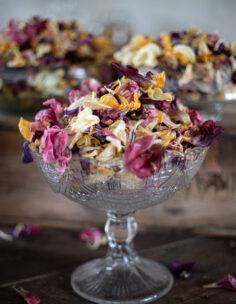 En glasskål på fot fylld till brädden med potpurri av blomster.