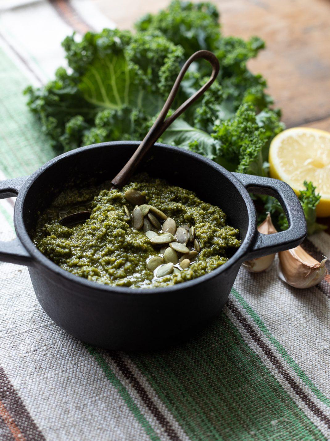 Pesto av grönkål i en svart bytta. Bredvid syns kålblad, citron och vitlöksklyftor.