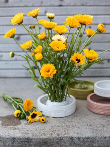Gula ringblommor i en blomhållare och fat i handgjord keramik.