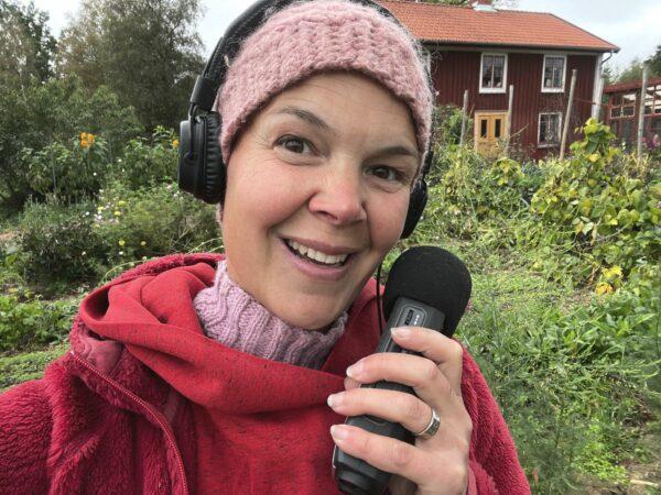Selfie på Sara i röda kläder och hörlurar, med inspelningsutrustning i handen.